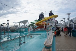 View of twin rectangular pools and water slides from a distance on pool deck of Norwegian Epic.jpg
