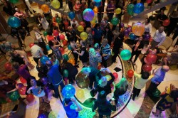 Adults playing & popping balloons at Sapphire Princess Piazza level.jpg
