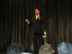 Carnival Pride Cruise Director Kirk Benning on stage in black suit.jpg