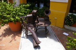 Metal statue art of a man sitting next to table with phonograph at Plaza de la Aduana in Cartagena Colombia.jpg