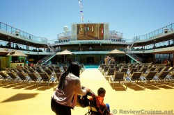 Large Flat Screen overlooking pool deck of Carnival Breeze.jpg