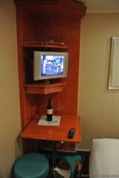 Small flat screen TV and  small desk in corner of Norwegian Gem inside cabin.jpg