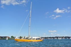 Orange sailboat with tourists aboard off the coast of Newport Rhode Island.jpg
