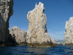 Tall rock formations of the Cabo San Lucas coast with cruise ships in the background.JPG