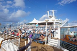 People relaxing on lounge chairs above pool deck on Norwegian Dawn.jpg